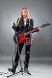 Schöne junge, blonde Frau mit einer E-Gitarre Stockbilder