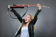 Schöne junge, blonde Frau mit einer E-Gitarre Stockbild