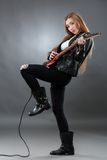 Schöne junge, blonde Frau mit einer E-Gitarre Stockfotografie