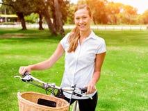Schöne junge blonde Frau mit Fahrrad im Park Lizenzfreie Stockbilder