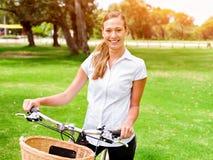 Schöne junge blonde Frau mit Fahrrad im Park Stockbild
