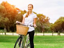 Schöne junge blonde Frau mit Fahrrad im Park Lizenzfreies Stockbild