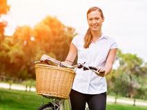 Schöne junge blonde Frau mit Fahrrad im Park Lizenzfreies Stockfoto