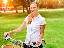 Schöne junge blonde Frau mit Fahrrad im Park Stockfoto