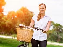Schöne junge blonde Frau mit Fahrrad im Park Lizenzfreie Stockfotografie