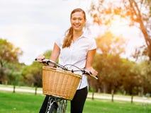 Schöne junge blonde Frau mit Fahrrad im Park Stockbilder