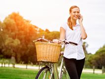 Schöne junge blonde Frau mit Fahrrad im Park sprechend über Telefon Lizenzfreies Stockfoto