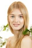 Schöne junge blonde Frau mit Frühlingsblumen Stockfotografie