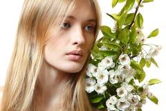 Schöne junge blonde Frau mit Frühlingsblumen Lizenzfreies Stockfoto
