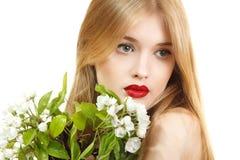 Schöne junge blonde Frau mit Frühlingsblumen Lizenzfreie Stockfotografie
