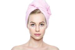 Schöne junge blonde Frau mit Gesichtscreme traf unter ihren Augen zu Gesichtsbehandlung Stockfotografie