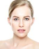 Schöne junge blonde Frau mit Gesichtscreme traf unter ihren Augen zu Gesichtsbehandlung Schönheit und Badekurortkonzept Stockbild