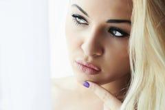 Schöne junge blonde Frau mit grünen Augen und Maniküre. Nahaufnahmemake-up. Tageslicht Stockbild