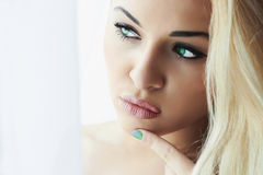Schöne junge blonde Frau mit grünen Augen und Maniküre. Nahaufnahmemake-up. Tageslicht Lizenzfreie Stockbilder