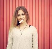 Schöne junge blonde Frau mit Kaugummi auf den Lippen, die nahe roter Wand aufwerfen outdoor Lizenzfreie Stockbilder
