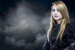 Schöne junge blonde Frau mit Lederjacke und Gitarre Lizenzfreies Stockfoto