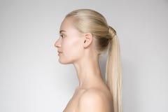 Schöne junge blonde Frau mit Pferdeschwanz-Frisur Lizenzfreie Stockfotos