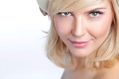 Schöne junge blonde Frau mit Pfirsichmake-up und weißer Kappe Lizenzfreie Stockfotos
