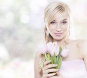 Schöne junge blonde Frau mit Tulpeblumenstrauß Lizenzfreie Stockfotografie