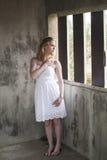 Schöne junge blonde Frau mit weißem Kleid Stockbilder