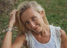 Schöne junge blonde Frau sitzt auf dem grünen Gras und betrachtet die Kamera mit schönen grauen Augen Moderner Lebensstil Lizenzfreies Stockbild