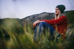 Schöne junge blonde Frau sitzt im Freien auf dem Hintergrund des Berges Lizenzfreies Stockfoto