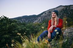 Schöne junge blonde Frau sitzt im Freien auf dem Hintergrund des Berges und des Waldes Lizenzfreie Stockfotografie