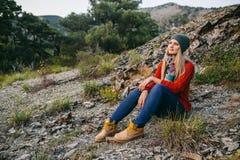 Schöne junge blonde Frau sitzt im Freien auf dem Hintergrund des Berges und des Waldes Stockfotografie