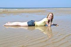 Schöne junge blonde Frau am Strand Stockfoto