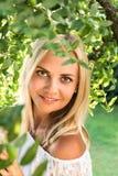Schöne junge blonde Frau unter dem Baum mit Stockbild