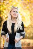 Schöne junge blonde glückliche Frau im Freien am Frühherbstnachmittag Stockfoto