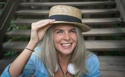 Schöne junge blonde Hippie-Frau in einem Strohhut, der auf den hölzernen Schritten im Park lächelnd sitzt, Kamera betrachtend Lizenzfreie Stockfotografie