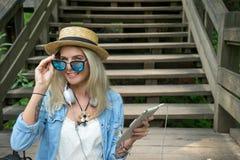 Schöne junge blonde Hippie-Frau mit den Gläsern, die in der Hand Kamera im Park mit Tablette, sitzend auf betrachten Stockfoto