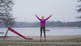 Schöne junge blonde kaukasische Eignungsfrau, die im Freien in der schwedischen Winterlandschaft ausbildet und springt stock video