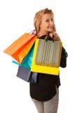 Schöne junge blonde kaukasische Frau, die das vibrierende Einkaufen hält Stockfotos