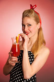Schöne junge blonde kaukasische Pinupfrau mit einem Glas Stockbild