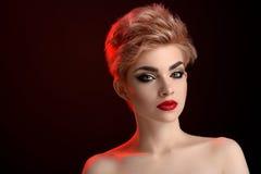 Schöne junge blonde rote lippige Frau, die in der künstlerischen roten Beleuchtung aufwirft Stockbilder