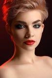 Schöne junge blonde rote lippige Frau, die in künstlerischem Rot L aufwirft Lizenzfreie Stockfotos