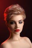 Schöne junge blonde rote lippige Frau, die in künstlerischem Rot L aufwirft Lizenzfreie Stockfotografie