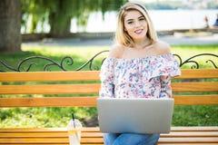 Schöne junge blonde Studentin, die tragbare Laptop-Computer beim Sitzen auf der Bank verwendet Junge schöne Mädchenanwendung pers Lizenzfreies Stockfoto
