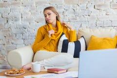 Schöne junge blonde Studentin, die tragbare Laptop-Computer beim Sitzen in einer Weinlesekaffeestube verwendet jung Lizenzfreie Stockfotos
