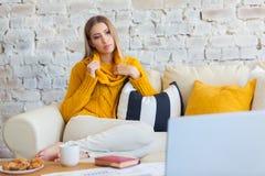 Schöne junge blonde Studentin, die tragbare Laptop-Computer beim Sitzen in einer Weinlesekaffeestube verwendet jung Stockbild