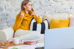 Schöne junge blonde Studentin, die tragbare Laptop-Computer beim Sitzen in einer Weinlesekaffeestube verwendet jung Stockbilder