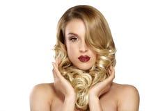 Schöne junge blonde vorbildliche Aufstellung des gelockten Haares Stockbild