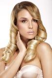 Schöne junge blonde vorbildliche Aufstellung des gelockten Haares Lizenzfreie Stockfotos