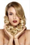 Schöne junge blonde vorbildliche Aufstellung des gelockten Haares Lizenzfreie Stockbilder