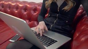 Schöne junge Blondine auf rotem Sofa unter Verwendung des Laptops und des Essens eines grünen Apfels im Wohnzimmer lizenzfreie stockfotografie