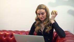 Schöne junge Blondine auf rotem Sofa unter Verwendung des Laptops und des Essens eines grünen Apfels im Wohnzimmer lizenzfreie stockfotos