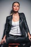 Schöne junge Blondine in der ledernen Kleidung, die auf Schemel sitzt lizenzfreies stockfoto