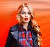 Schöne junge Blondine des Modeporträts, welche die roten Lippen machen den Kuss trägt eine schwarze Felsenart über buntem durchbr Stockfotos
